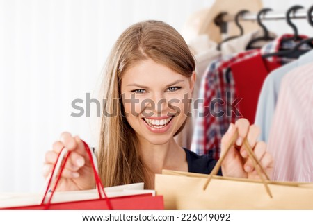 Close up portrait of young spree shopper holding shopping bags in fashion store. Pretty smiling woman buyer making purchase in clothing boutique.  - stock photo