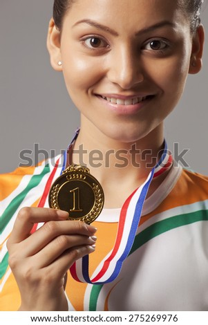 Close-up portrait of young woman holding gold medal isolated over gray background - stock photo