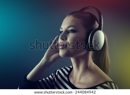 Close up portrait of young woman musician recording music in studio. Pretty female performer wearing headphones enjoying stereo beat.  - stock photo