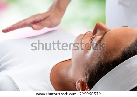 Close up portrait of young woman relaxing at reiki session with therapist hand in background. - stock photo