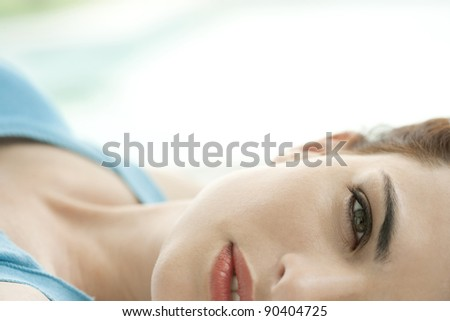 Close up portrait of young woman's half face laying down at home. - stock photo