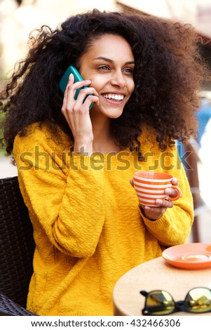 Close up portrait of young woman talking on the phone in coffee shop