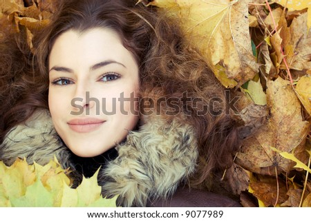close-up portrait of young woman with autumn leaves - stock photo