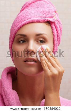 Close-up portrait of young woman with perfect health skin of face, bath towel on head and clean sponge. - stock photo
