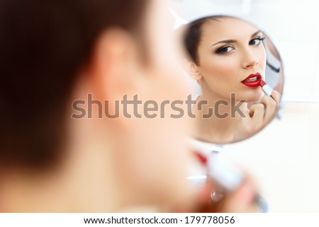 Close up Portrait of Young Woman With Red Lips. Beautiful Woman Doing Daily Makeup. Lipstick applying - stock photo