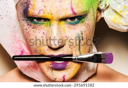Close-up portrait of young woman with unusual makeup. Model holding makeup brash in her mouth. Woman posing with paint drops over her face. Creative makeup - stock photo