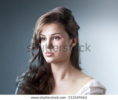 close up portrait on blue background , serious look of young girl - stock photo