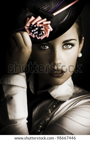 Close-up portrait on the face of a beautiful and mysterious female standing in the shadows halfway between dark and light wearing a stylish flower hat in a image titled face of dark fashion - stock photo