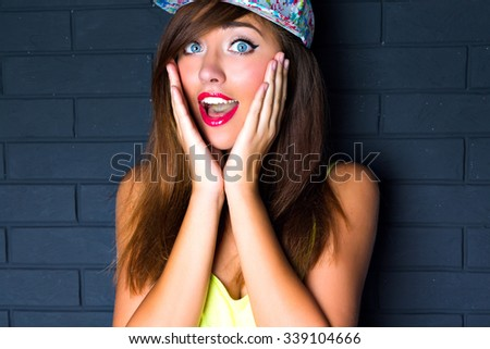 Close up portrait os sexy smiling woman, laughing out her hands to the cheeks surprised emotions, bright make up, long hairs swag retro hat. Bright toned colors. - stock photo