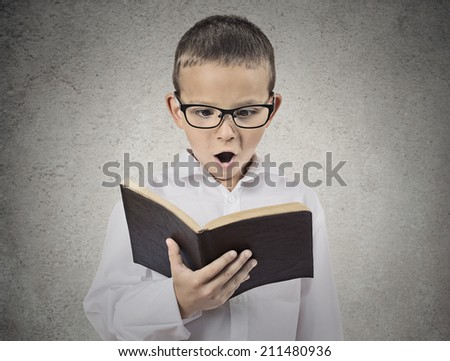 Close up portrait surprised young man with glasses holding, reading old book isolated grey wall background. Face expressions, human emotions, body language. Education, knowledge, information concept - stock photo