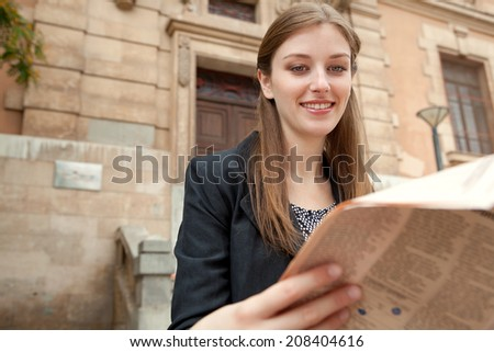 Close up portrait view of an attractive professional young woman sitting by a classic stone building in the city reading a financial newspaper, smiling outdoors. Business communications and news.