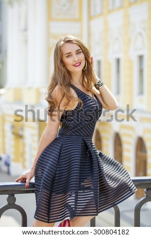 Close up Portrait, Young beautiful blonde woman in black dress posing outdoors in sunny weather - stock photo