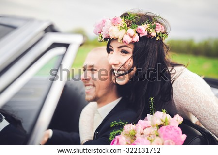 close-up portrait young beautiful stylish couple bride in a white dress with a bouquet of flowers in her hair and and groom in retro car on the way to their honeymoon - stock photo