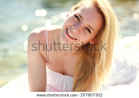 Close-up portrait young blond woman resting happily on the sea beach, enjoying summer vacation