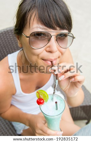Close-up portrait young pretty woman drinking cocktail at outdoor cafe      - stock photo