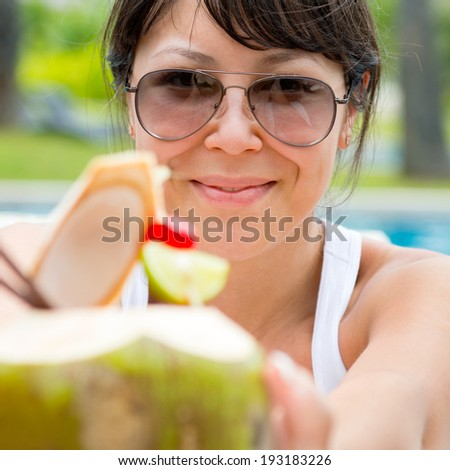 Close-up portrait young pretty woman drinking coconut cocktail against outdoor pool