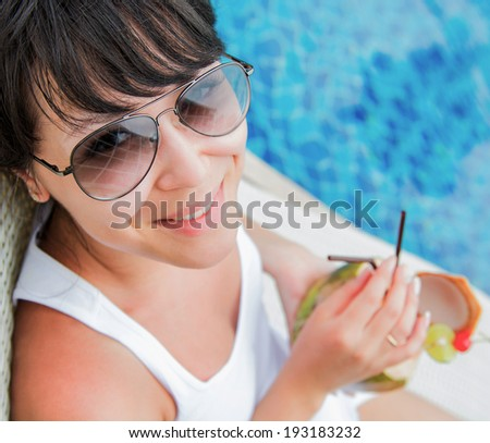 Close-up portrait young pretty woman drinking coconut cocktail against outdoor pool. Top view . Concept photo recreation and tourism - stock photo