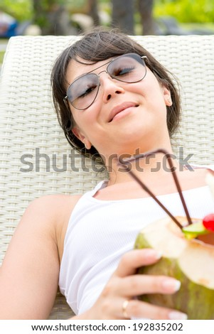 Close-up portrait young pretty woman with sunglasses  lie on sun lounger and coconut cocktail oudoor - stock photo