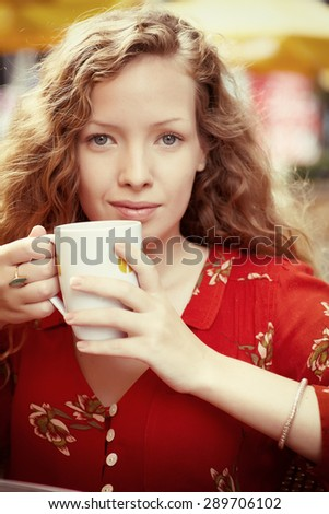 Close up portrait young woman sitting in outside cafe with cup of drink