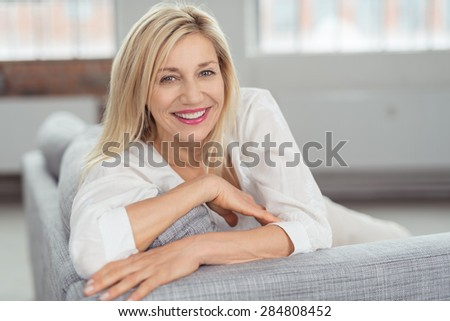 Close up Pretty Blond Adult Woman Sitting on Gray Couch, Looking at Camera with a Happy Facial Expression.