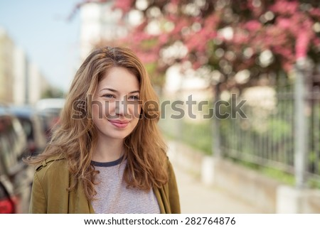 Close up Pretty Blond Girl Walking at the Street, Smiling Into the Distance, Emphasizing Thinking Something Good. - stock photo