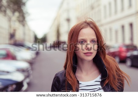 Close up Pretty Blond Young Woman Walking at the Street While Looking Into the Distance with Serious Facial Expression. - stock photo