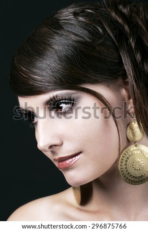 Close up Pretty Face with Makeup of a Young Woman with Big Gold Earrings, Looking to the Left of the Frame Against Black Background. - stock photo