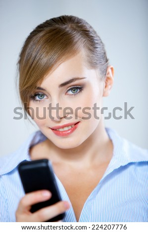 Close up Pretty Smiling Woman in Stripe Blouse Using Black Mobile Phone While Looking at Camera. Captured in Studio on Gradient Gray Background. - stock photo