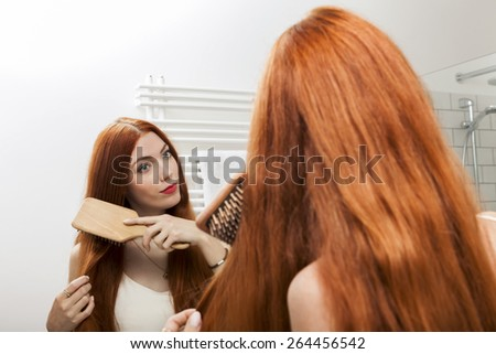 Close up Pretty Young Woman Brushing her Long Blond Hair In Front a Large Mirror in the Room. - stock photo