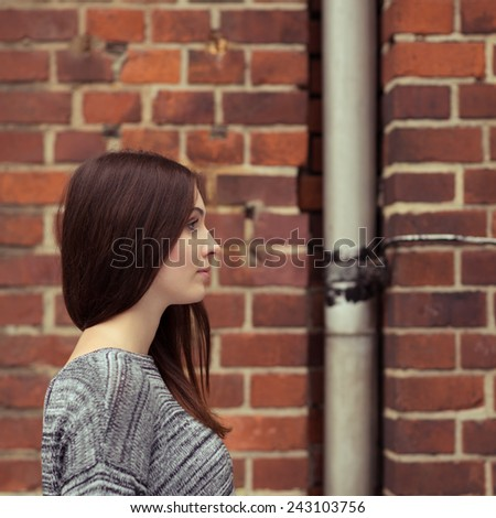 Close up Pretty Young Woman Wearing Gray Tops in Side View, Looking Right Frame, on Brick Wall Background - stock photo