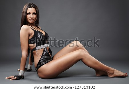 Close-up profile of hot exotic dancer in leather lingerie sitting on the ground, facing the camera - stock photo