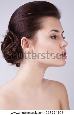 Close up profile of pretty young female with natural look and fashionable hairstyle - stock photo