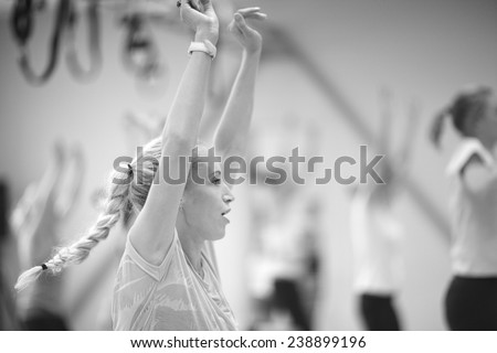 Close up profile of young woman lifted arms, group fitness concept, monochrome - stock photo