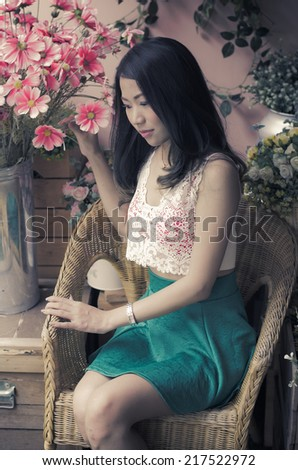 Close up profile portrait of a beautiful and young woman enjoying and smelling a bouquet of flowers while standing in a fresh floral market sit during a summer day . - stock photo