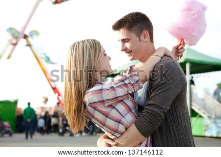 Close up profile portrait view of an attractive couple hugging and smiling while holding a cotton candy sweet in an attractions park during a sunny day. - stock photo
