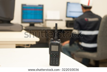 Close up radio communication with the engineers check the server in the background. - stock photo
