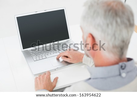 Close-up rear view of a grey haired man using laptop at desk against white background - stock photo
