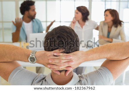 Close-up rear view of a relaxed businessman with colleagues in meeting in background at the office - stock photo