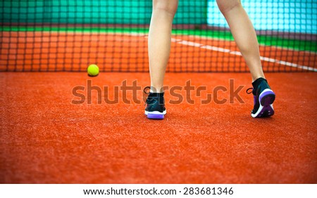 Close-up rear view of beautiful woman in sports clothing playing tennis on court - stock photo