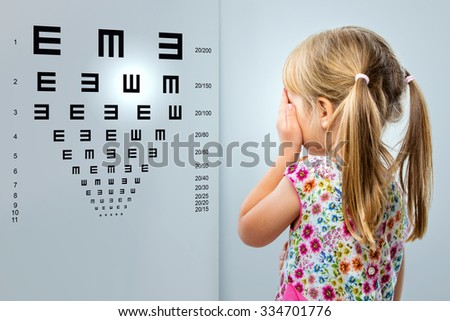 Close up rear view of little girl looking at eye test chart.Kid closing one eye with hand. - stock photo