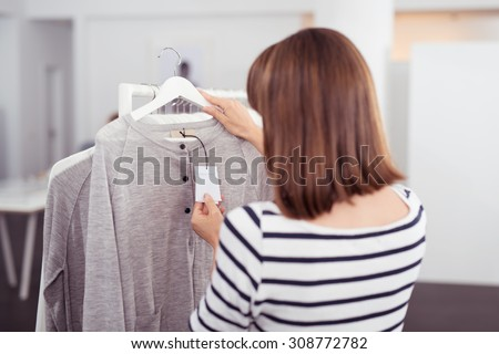 Close up Rear View of Woman Looking at the Price Tag of a Trendy Gray Shirt Hanged on Rail Inside the Clothing Store. - stock photo