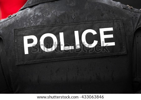 Close up rear view on police jacket with large text partially covered in water from rain - stock photo