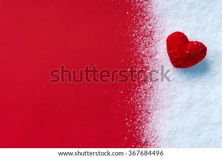 Close up Red heart of red wool yarn on white snow winter and red background. Love and St. Valentines Day concept. - stock photo