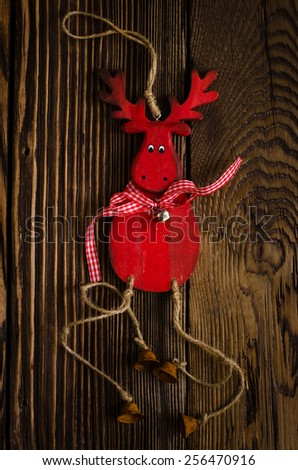 Close up Red Wooden Deer Hanging Decor with Small Bells, Placed on Top of Textured Wooden Table. - stock photo