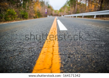 Close up road in autumn with yellow line - stock photo
