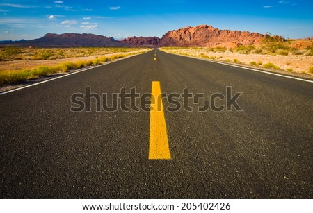 Close up road view of yellow center lines with mountains in distance. - stock photo