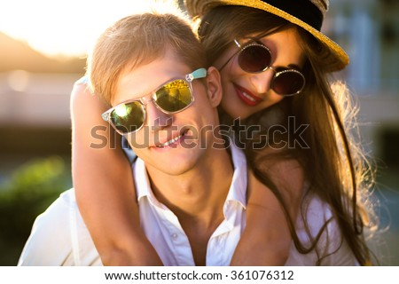 Close up romantic beauty portrait of happy hipster couple in love hugs and having fun, evening sunlight, stylish sunglasses, hat, emotions, joy, youth, sunny colors, hugs and kisses, vintage style. - stock photo