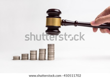 Close up row of coins and hand of young man holding lawyer gavel wooden, auction concept. - stock photo