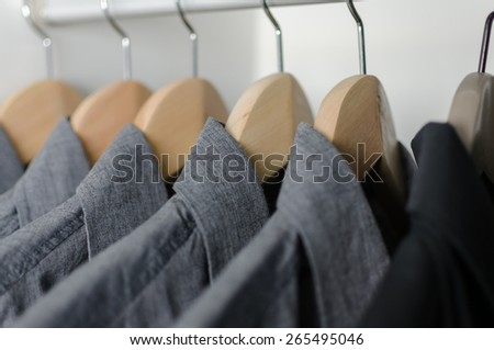 close up row of grey and black shirts hanging on coat hanger in white wardrobe - stock photo