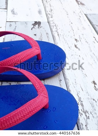 Close up : Rubber slippers on old wood background